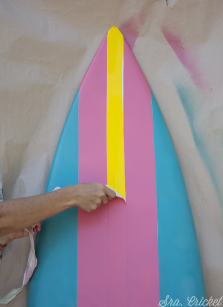 peeling masking tape on spray painted surf board